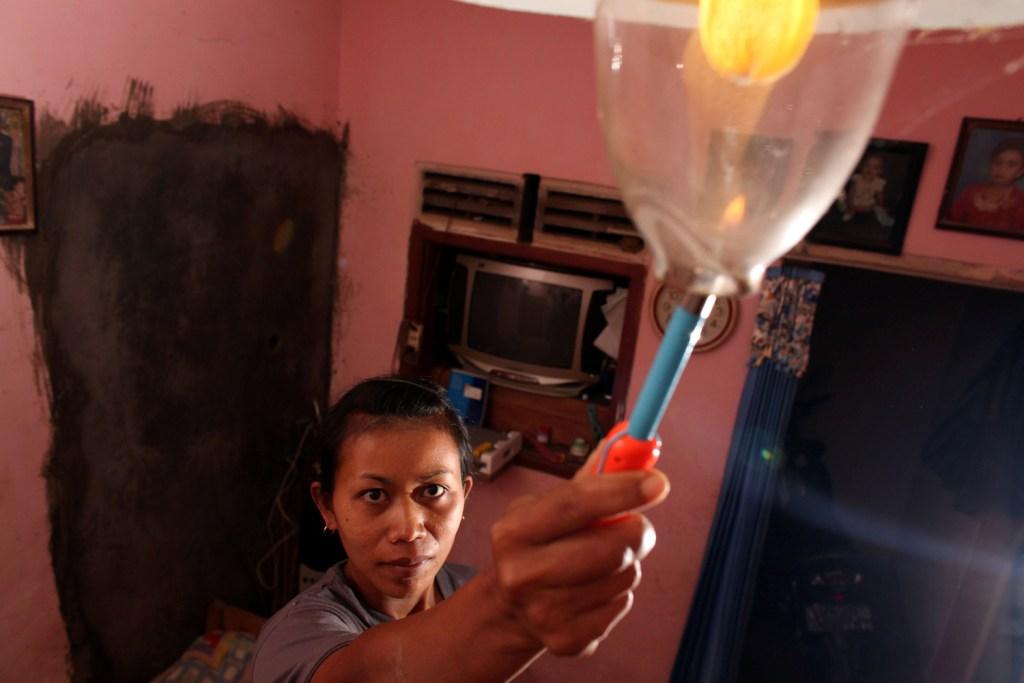 Seorang perempuan menyalakan lampu biogas di ruang makan rumahnya di Jawa Timur.