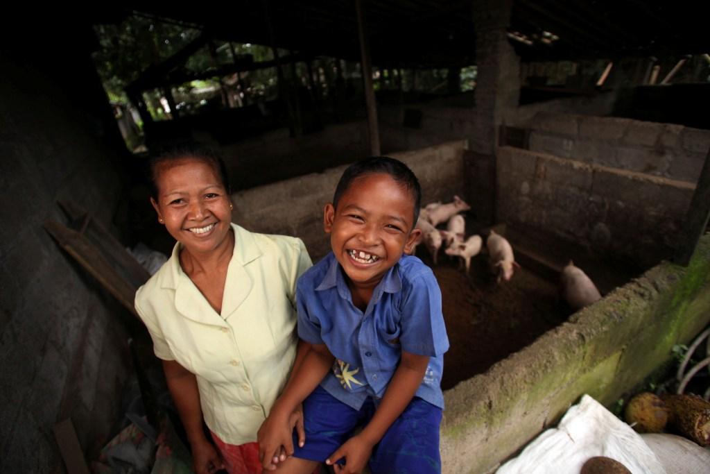 Seorang ibu dan anak tertawa di depan kandang babi mereka di Bali. Memanfaatkan limbah menjadi energi adalah konsep yang sejalan dengan cara hidup masyarakat Bali yang selalu menjaga kelestarian dan keseimbangan alam.