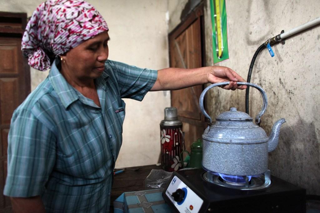Seorang ibu sedang memasak air untuk kopi menggunakan kompor biogas di Jawa Timur. Biogas, cara moden dan lebih sehat untuk memasak.