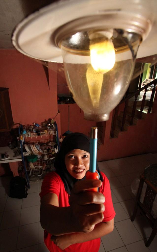 """Fatchiyah, 32, menyalakan lampu biogas di ruang tengah rumahnya di Desa Tlogosari, Nongkojajar, Pasuruan, Jawa Timur. """"Saya harap ekonomi keluarga kami semakin lama semakin baik. Nanti, saya mau beli sebuah truk pick-up untuk usaha""""."""