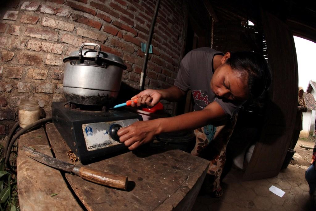 Seorang perempuan menyalakan kompor biogas yang ada di kandang ternaknya. Untuk memenuhi kebutuhan energi, keluarga peternak umumnya menggunakan kombinasi bahan bakar gas cair (LPG) untuk memasak dan kayu bakar untuk merebus air untuk keperluan sapi perah