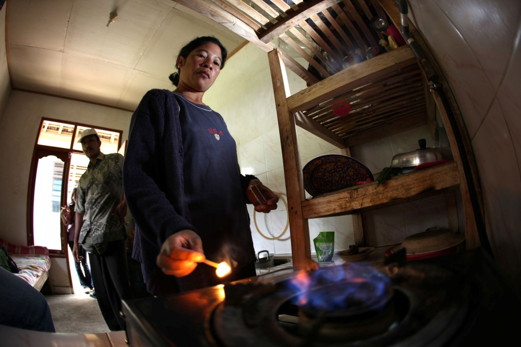 A woman in Bali lights up the biogas stove for cooking.