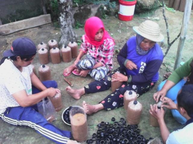 Ibu-ibu dari kelompok Kartika Manunggal sedang membuat medium budidaya jamur (foto – Witono Sasongko)