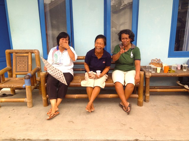 Ibu Atun, kanan, duduk-duduk di luar dapur yang mengolah susu (foto: Joshua Parfitt)